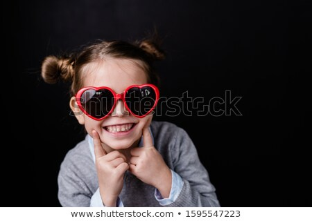 Cute cheerful girl with toothy smile looking through stylish sunglasses Stock photo © pressmaster