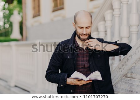 Handsome clever bald male holds book, reads interesting novel with serious expression, stands outdoo Stock photo © vkstudio