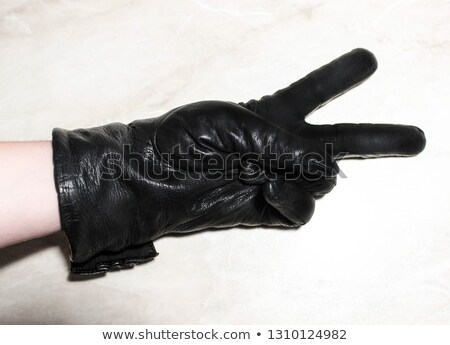 Sign victory made female's hand in rubber protective glove. Stock photo © artjazz