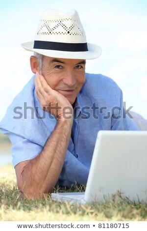 Senior man using his laptop lying on the grass Stock photo © photography33