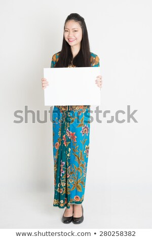 Southeast Asian woman holding a white blank card Stock photo © szefei