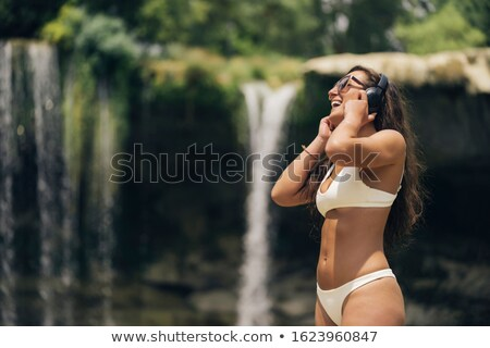 Happy young girl with green bikini listening to music Stock photo © nenetus