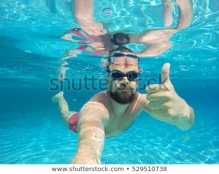 Fiatal szakállas férfi búvárkodik kék tiszta víz Stock fotó © vlad_star