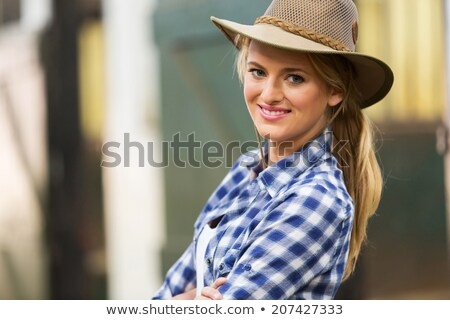Beautiful young woman cowgirl in hat and plaid shirt Stock photo © deandrobot