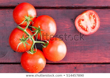 Half of a tomato with cluster over dark table Stock photo © ozgur