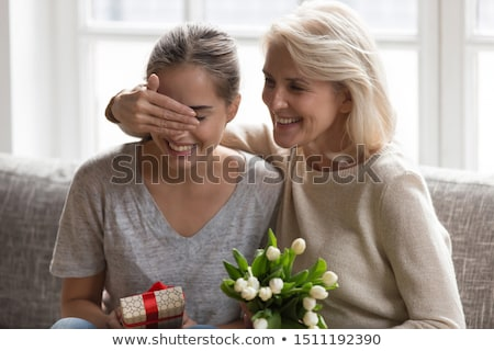 Mother giving daughter flowers and smiling Stock photo © monkey_business