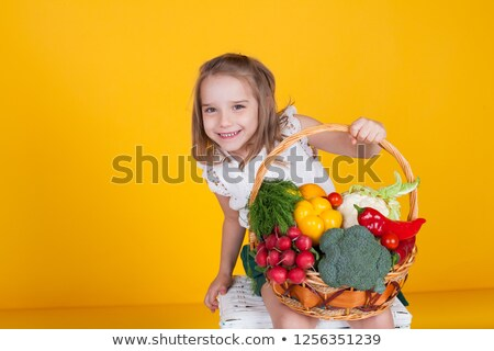 Girl carrying wicker basket with cucumbers stock photo © przemekklos