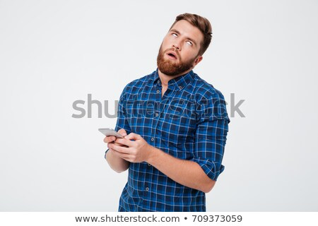 Dissatisfied bearded man in checkered shirt using smartphone Stock photo © deandrobot