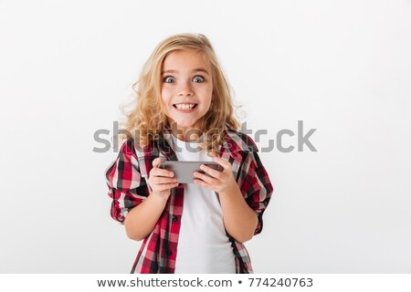 Portrait of an excited little girl holding mobile phone Stock photo © deandrobot