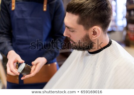 barber showing hair styling wax to male customer Stock photo © dolgachov