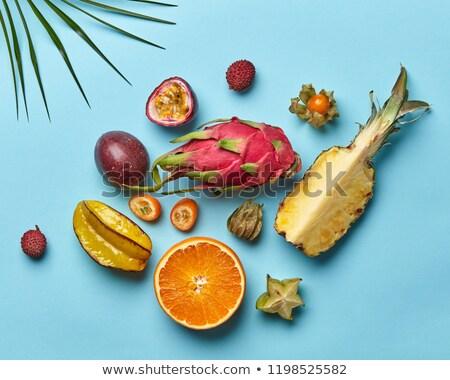 Whole and halves of exotic healthy fruits, carambola, pineapple, passion fruit, pitahaya, palm green Stock photo © artjazz