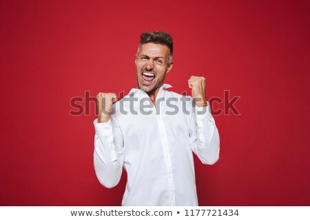 Photo of positive guy in formal wear shouting and clenching fist Stock photo © deandrobot