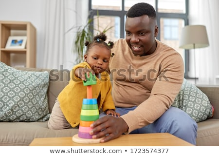 baby girl with parents playing with pyramid toy stock photo © dolgachov