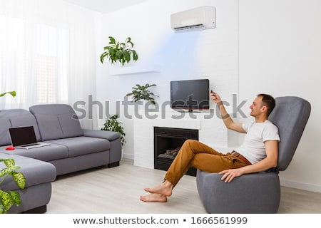 Man Using Laptop Enjoying Cooling Under Air Conditioner Stock photo © AndreyPopov