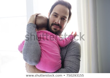 father consoling his baby girl close to the window stock photo © lopolo