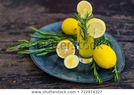 Stock photo: Liqueur limoncello with pieces of lemon and rosemary herb