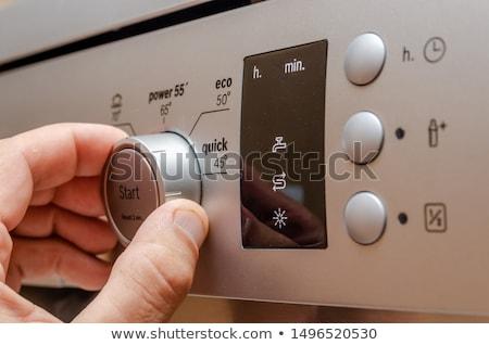 Adam düğme bulaşık makinesi genç mutfak Stok fotoğraf © AndreyPopov