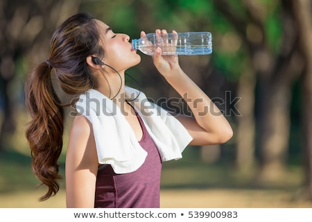 woman drinking water after exercising on beach Stock photo © dolgachov