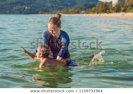 Stockfoto: Woman Swimming Instructor For Children Is Teaching A Happy Boy To Swim In The Sea
