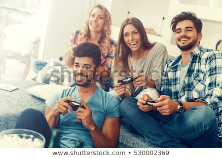 Stock photo: Couple playing video games at home, sitting on sofa