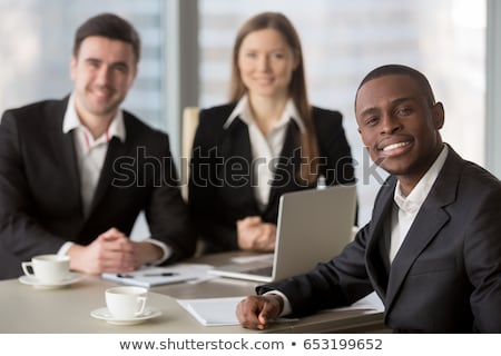 Positive young multi-ethnic marketing experts sitting at table Stock photo © pressmaster