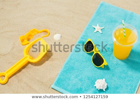 sunglasses sand toys and juice on beach towel stock photo © dolgachov