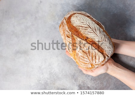 Baker man holding homemade rustic wheat bread in hands. Selective focus Stock photo © galitskaya