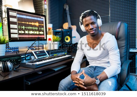 Happy young successful musician or producer in headphones sitting by workplace Stock photo © pressmaster