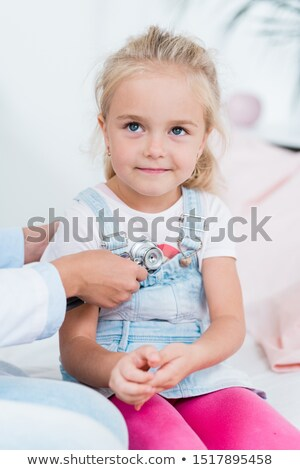 Adorable little girl with blond hair sitting on bed in medical office Stock photo © pressmaster