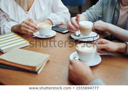 Hands of college friends gathered by table in cafe after classes for a drink Stock photo © pressmaster