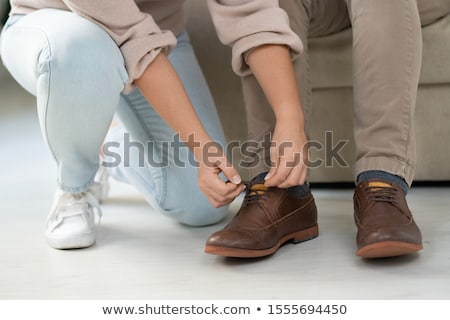 Young woman in casualwear helping her disable father to tie shoelaces on boots Stock photo © pressmaster