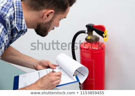 Man Checking Fire Extinguisher Writing On Document Stock photo © AndreyPopov