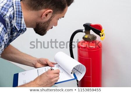 Férfi tűzoltó készülék ír irat közelkép technikus Stock fotó © AndreyPopov