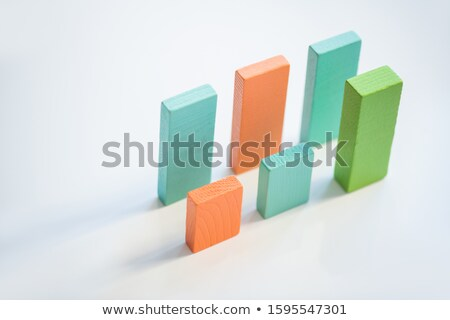 Two parallel rows of blue, orange and green flat wooden bricks making up charts Stock photo © pressmaster