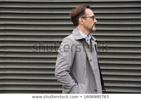 Image in profile of handsome businessman looking forward while standing Stock photo © deandrobot
