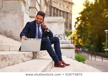 Image of handsome man holding smartphone while sitting on stairs Stock photo © deandrobot