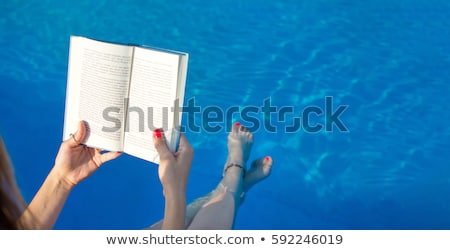Woman reading a novel by the poolside Stock photo © photography33