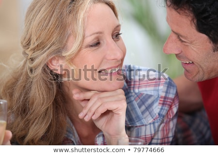 Smiling couple gazing intimately at each other with champagne glasses just in sight Stock photo © photography33