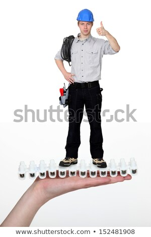 Handyman giving the thumbs-up whilst standing on giant hand Stock photo © photography33