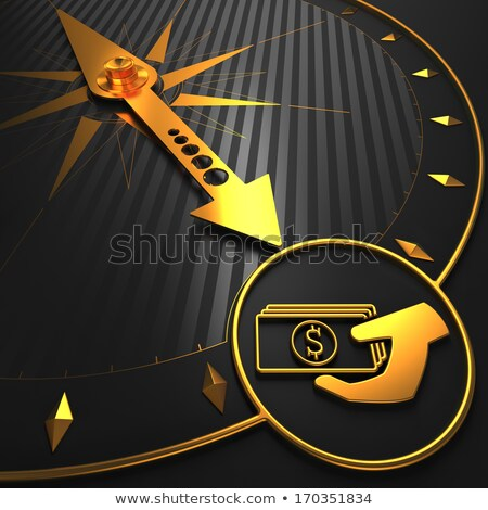 golden icon of money in the hand on black compass stock photo © tashatuvango