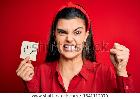 young woman holding paper with unhappy smiley stock photo © michaklootwijk