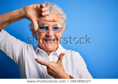 senior woman making frame with fingers stock photo © bmonteny