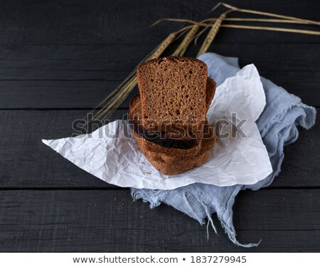 Loaf of homemade bread with black  on table with rye spikelets on the background . Stock photo © mcherevan