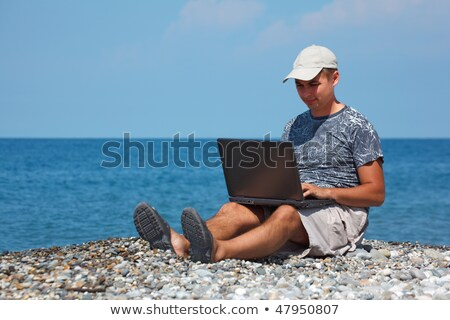 Man sitting on beach with laptop on his knees against  backdrop of sea. Stock photo © Paha_L