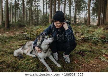 Young pretty woman hugging cute white puppy dog in autumn fall park. Stock photo © photocreo