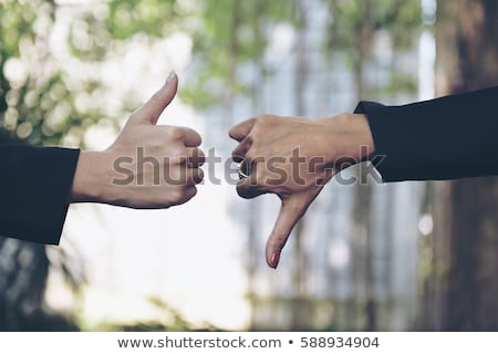 thumb down of a woman blurred in the background Stock photo © Giulio_Fornasar