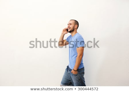 cheerful bearded young man talking by phone stock photo © deandrobot