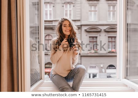 beautiful woman poses on a window sill stock photo © tekso