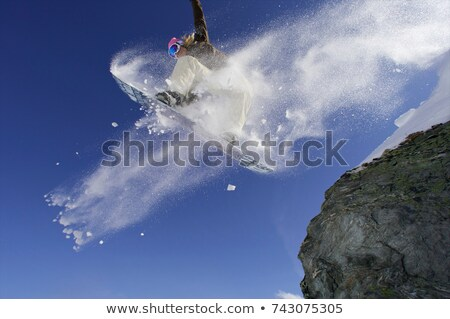 Female snowboarder jumping off a rock Stock photo © IS2