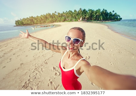photo of happy beautiful woman in white swimsuit and sunglasses stock photo © deandrobot